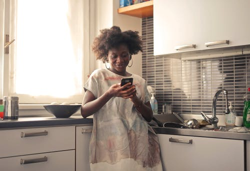 Woman in White T-shirt Holding Black Smartphone