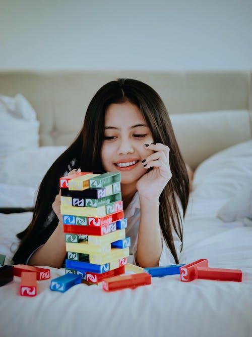 Girl in White Shirt Holding Lego Blocks