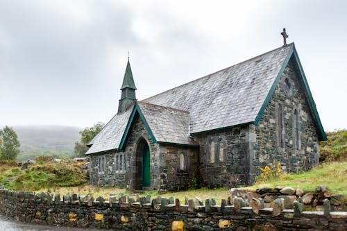 Exterior of aged church with shabby roof near stone fence in green grassy countryside in foggy day
