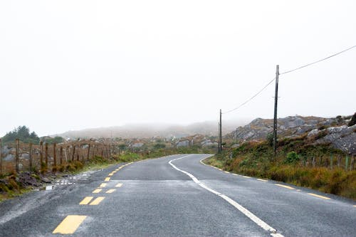 Empty part of ring of Kerry road in Ireland under cloudy sky in foggy weather
