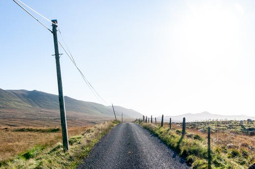 Picturesque scenery of empty road near grassy hills and mountains under blue sky