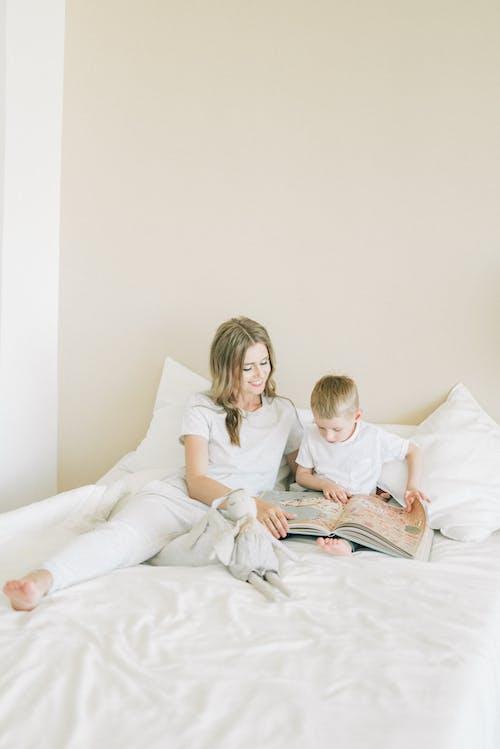 여자와 아이가 침대에 앉아