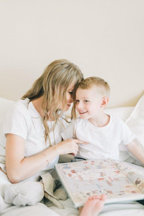 Woman In White T-shirt Sitting Beside Boy In White T-shirt