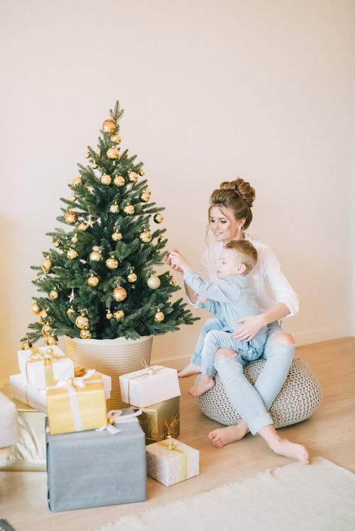 Mother And Child Decorating The Tree