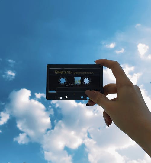Crop woman showing old audio tape under shiny sky