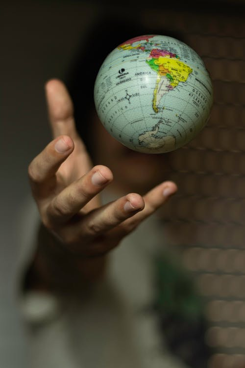 Person Holding White and Green Globe