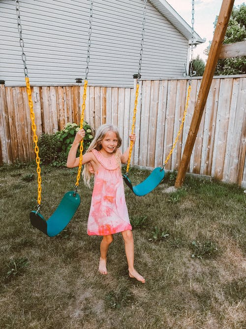 Girl in Pink Dress Riding on Swing