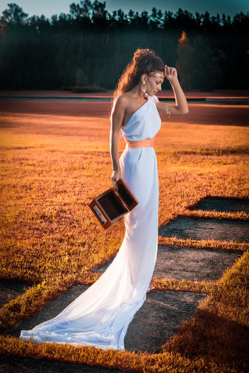 Woman in White Dress Holding Black Leather Bag