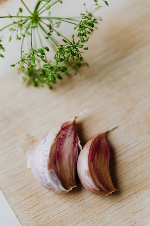 White and Red Garlic on Brown Wooden Table