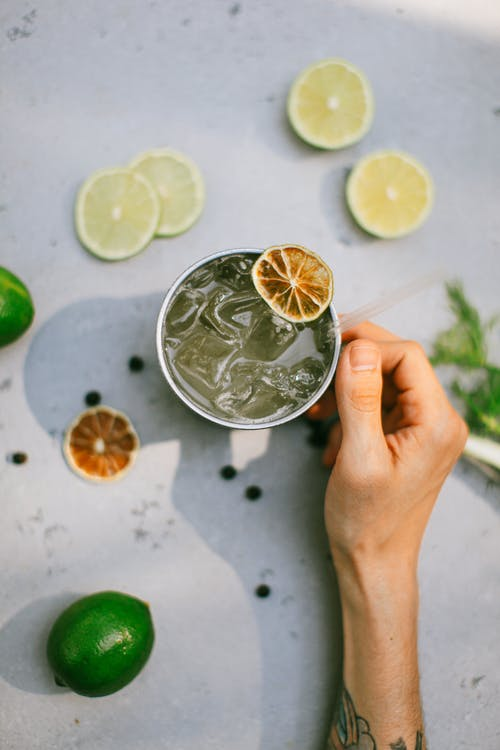 Person Holding Clear Drinking Glass With Sliced Lemon