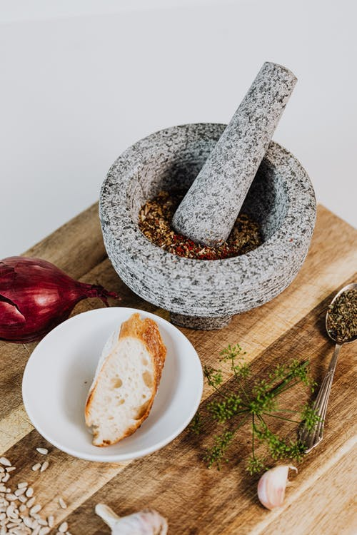 White and Gray Mortar and Pestle on Brown Wooden Table