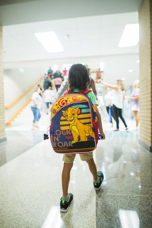 Unrecognizable child with backpack walking in crowded hall