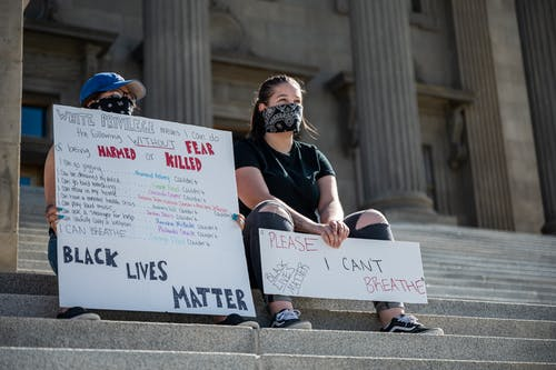 Anonymous protesters with BLM placards on stairs in city