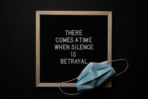Top view of sterile mask on chalkboard with There Comes A Time When Silence Is Betrayal inscription during COVID 19 pandemic