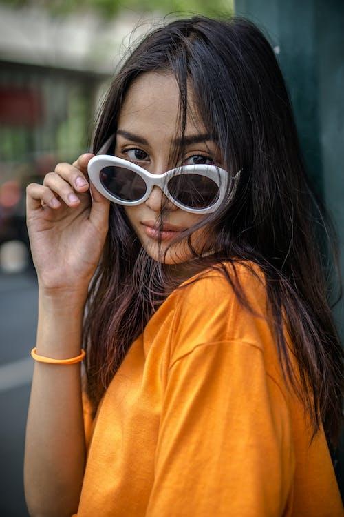 Woman in Orange Crew Neck T-shirt Wearing White Framed Sunglasses
