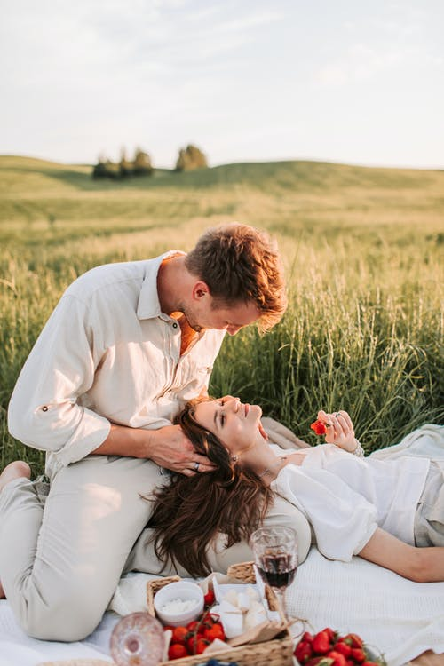 Man in White Dress Shirt Sitting on Womans Lap on Green Grass Field