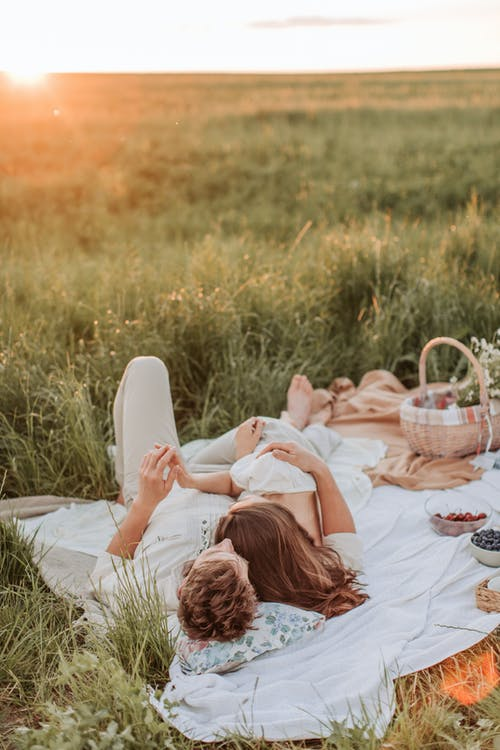 Man And Woman Lying On A Picnic Blanket