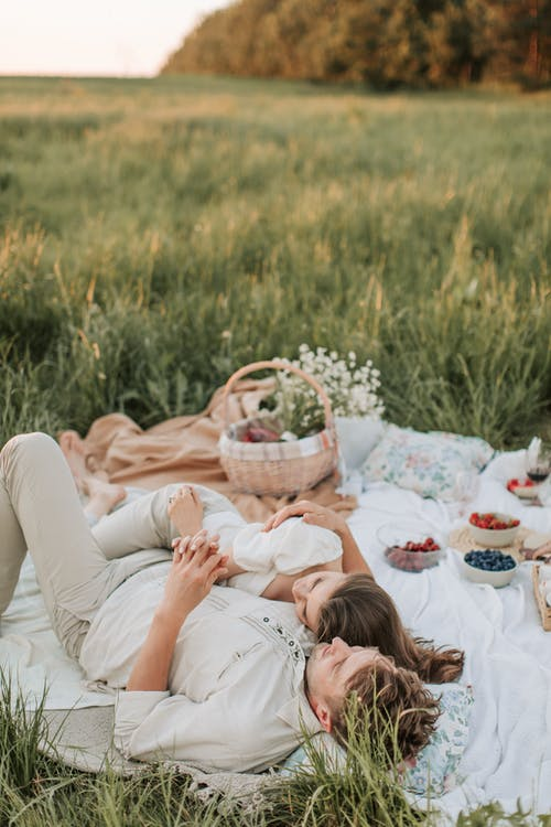 Man And Woman Lying On Picnic Blanket