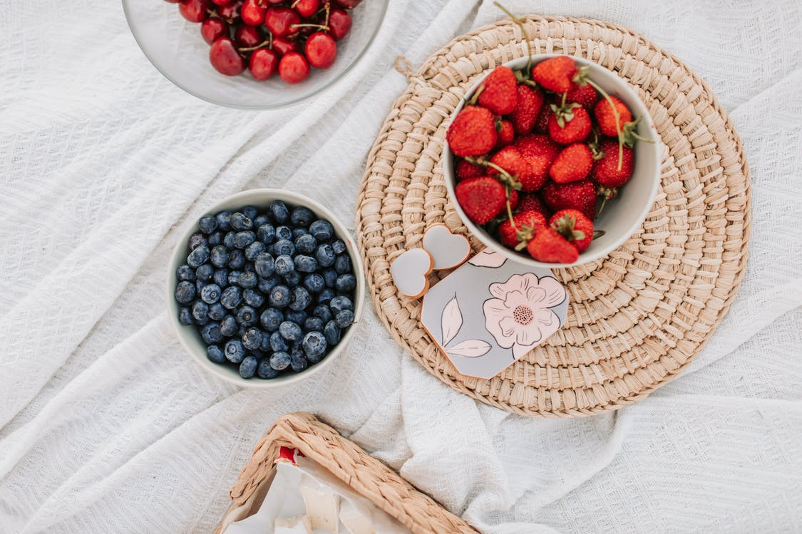 Red and Blue Berries on Brown Woven Basket