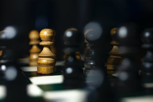Brown And Black Chess Pieces On Chess Board