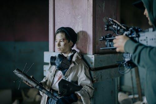 мальчик в коричневой куртке с черно серым ружьем
