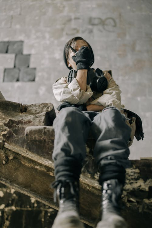 Man in Gray Jacket and Black Helmet Sitting on Concrete Stairs