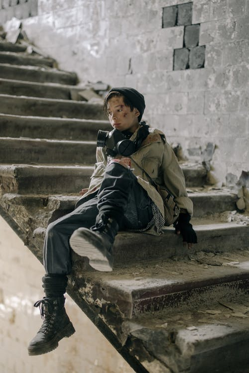Boy in Brown Jacket Sitting on Concrete Staircase