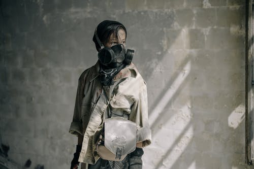 Woman in Brown Leather Jacket Wearing Black Gas Mask