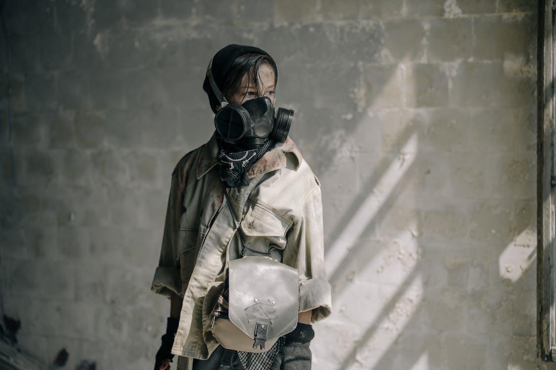 Wanita Dengan Jaket Kulit Coklat Mengenakan Masker Gas Hitam