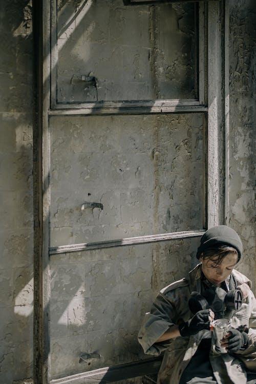 Man in Black Jacket and Black Cap Standing Beside Gray Steel Door