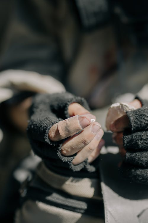 Person in Black Gloves Holding Hands