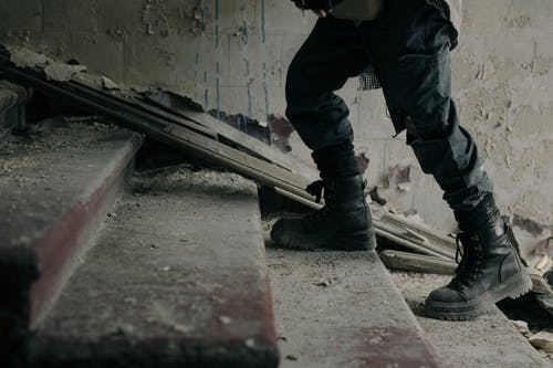 Person in Black Pants and Black Boots Standing on Gray Concrete Stairs