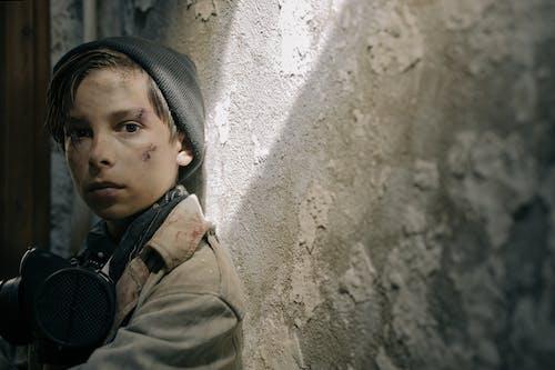 Boy in Green Jacket Leaning on Wall