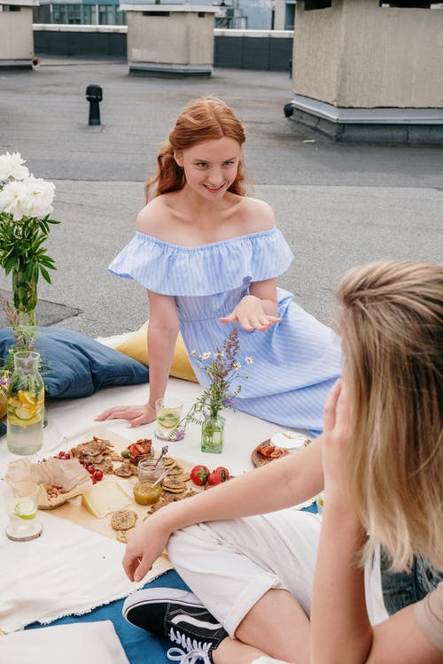 Woman in White Dress Sitting on Floor With Food on Table