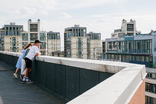 Man in White T-shirt and Black Pants Standing on Gray Concrete Bridge