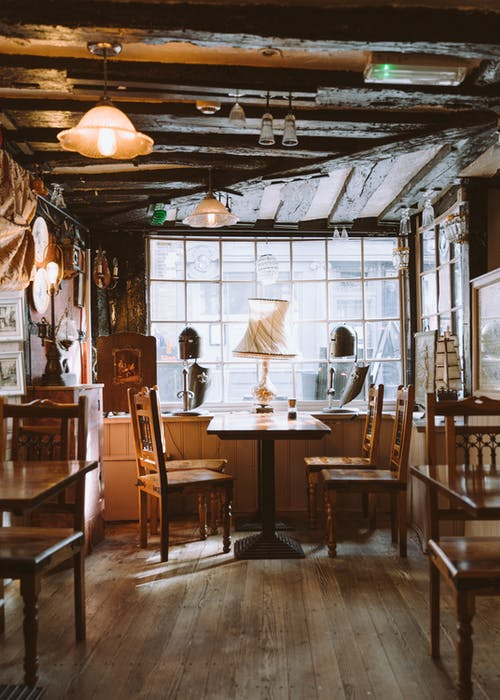 Vintage interior with comfortable wooden furniture and big windows of cozy restaurant in modern city in daylight