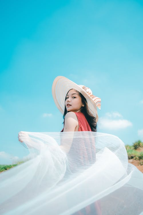 Stylish Asian teenager in hat with flying cloth on street