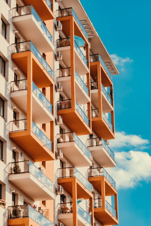 Low angle facade of modern brown and white condominium building with glass balconies against cloudless blue sky