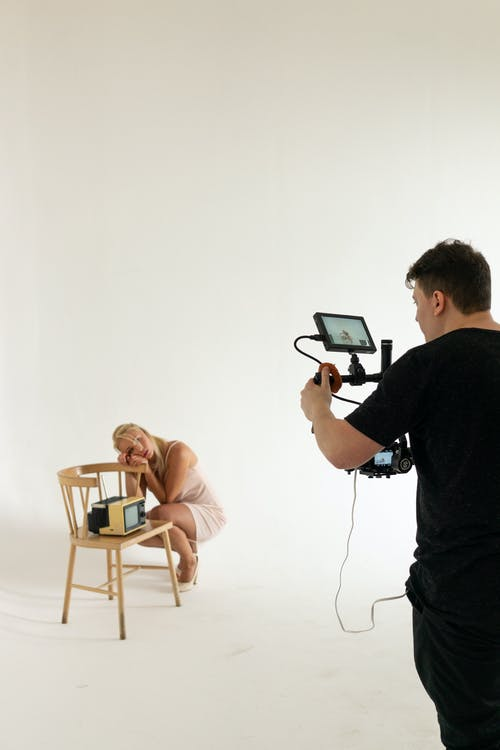 Back view of photographer with modern camera shooting dreamy model near chair with old fashioned TV