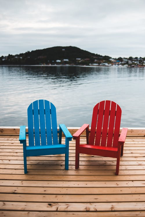 Two wooden armchairs placed on pier on picturesque scenery of lake and hill on cloudy day