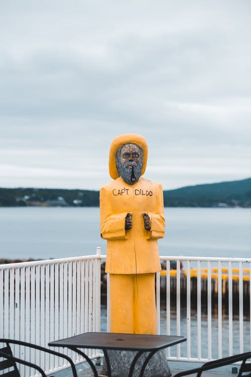 Statue of man with beard and tobacco pipe wearing yellow hat and clothes with funny sign reading Capt Dildo placed on scenery of lakeside