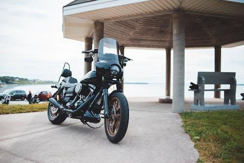 Black motorcycle on paved coastline