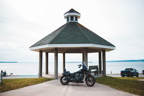 Cloudless clear sky over black classical motorcycle parked on road to tall rotunda on shore of big lake
