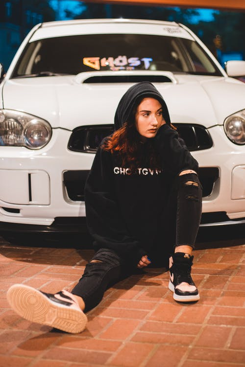 Full body of pensive young slender female in black hoodie and ripped jeans leaning on hand and thoughtfully looking away while resting on brick floor by luxury sports car