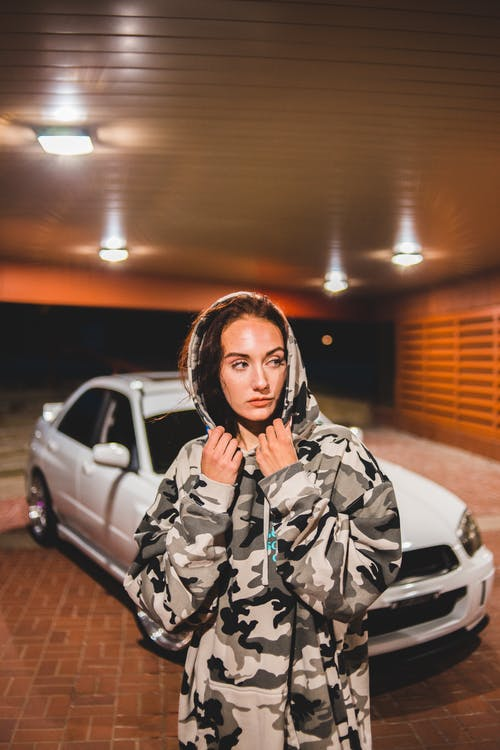 Pensive woman next to car on parking