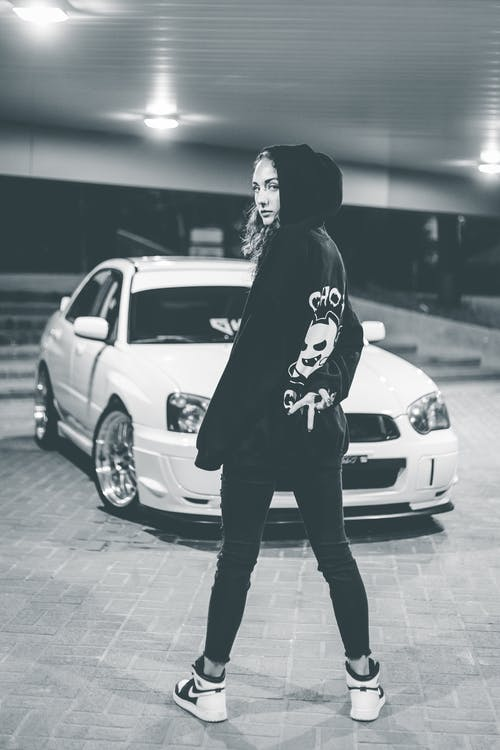 Black and white full body of dreamy young slender female in hoodie and jeans looking at camera over shoulder while standing by luxury white sports car in light of lamps