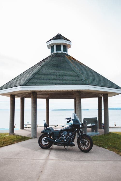 Classical motorcycle by rotunda next to lake