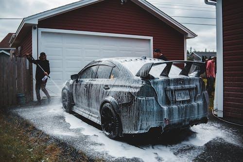 Faceless man washing luxury sports car in yard of house