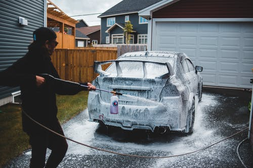 Side view of faceless male in black clothing washing car with foam in yard of house in daytime