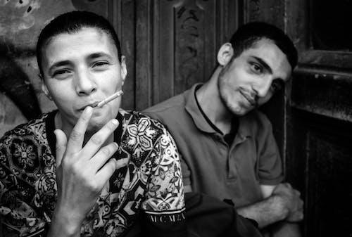 Smiling man smoking cigarette on street